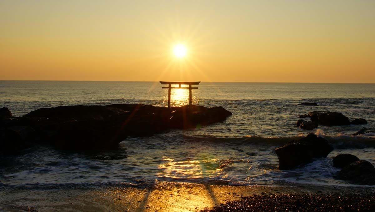 朝日に照らされる鳥居と海