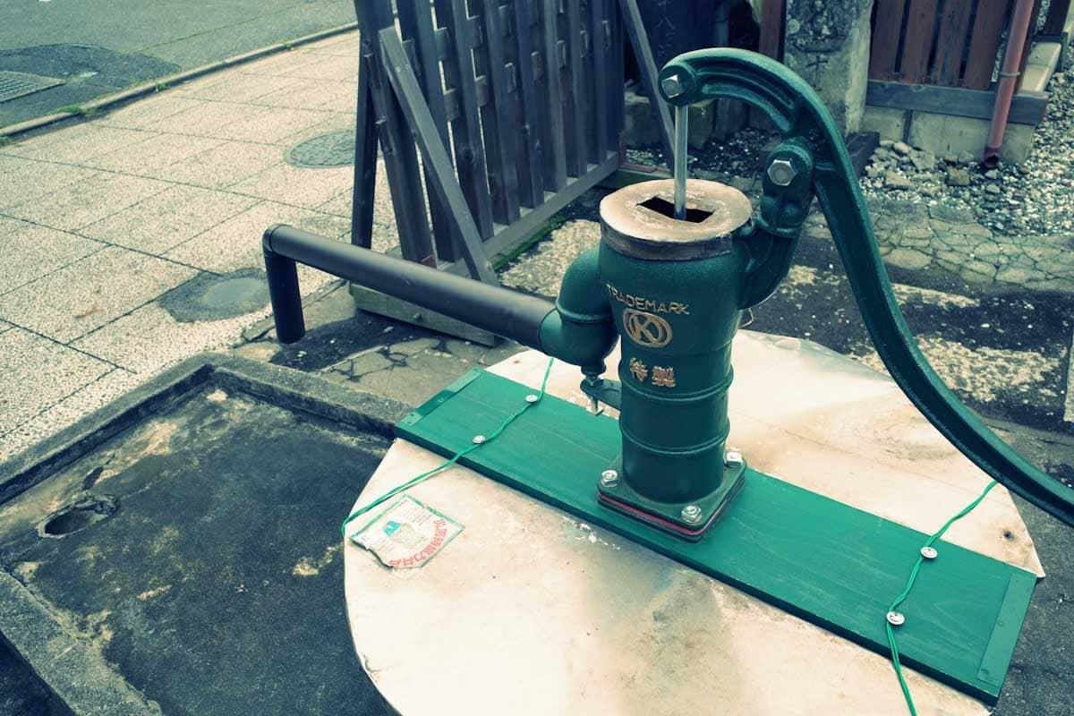 井戸を汲み上げる緑色のポンプ