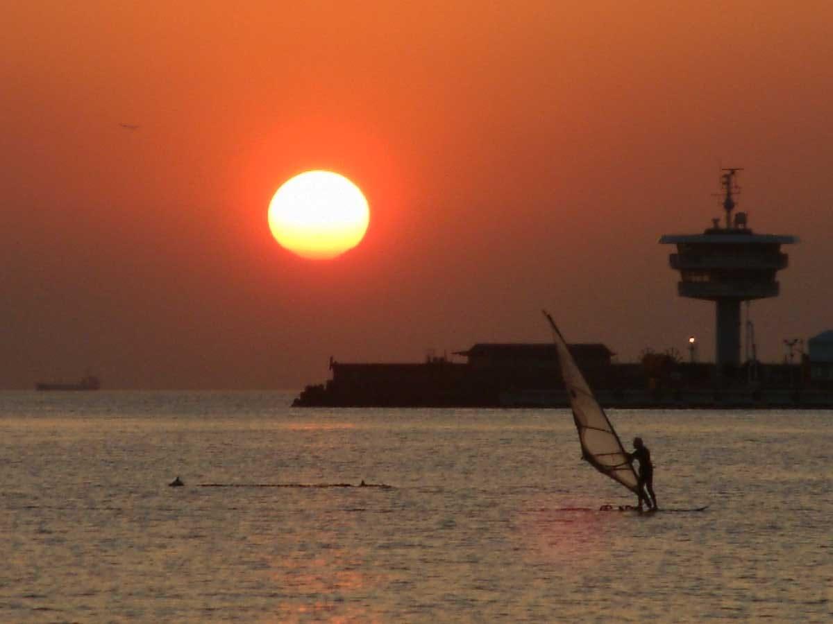 夕日とヨットに乗る男性
